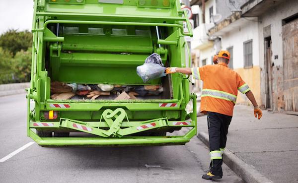 worker throwing trash in garbage truck